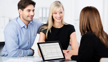 Mid adult couple smiling while looking at female financial advisor at desk in office